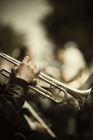 jazz band playing on the street, selective focus on the hands with trumpet ,film fx