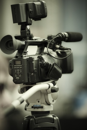 professional camcorder on the tripod, selective focus on nearest part Stock Photo
