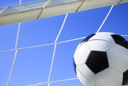 Soccer ball going into goal net ,selective focus photo