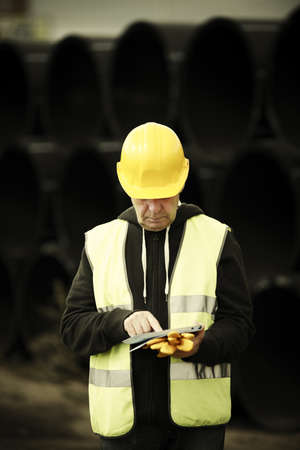 builder with small computer and gloves, selective focus on face Stock Photo