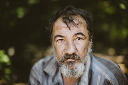 homeless man: real homeless man on the foliage background, selective focus on eye