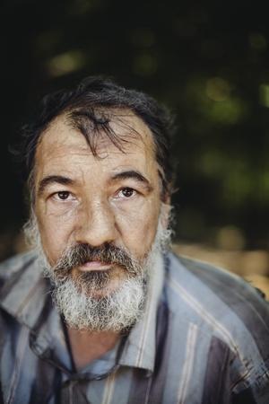 vagabundos: hombre sin hogar real en el follaje de fondo, el enfoque selectivo en el ojo