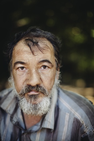 homeless: real homeless man on the foliage background, selective focus on eye