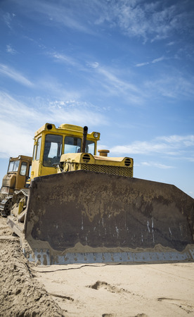 Bulldozer at work on blue sky background photo