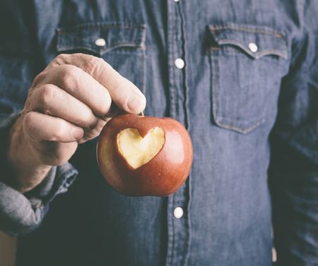 red apple with hand of man photo