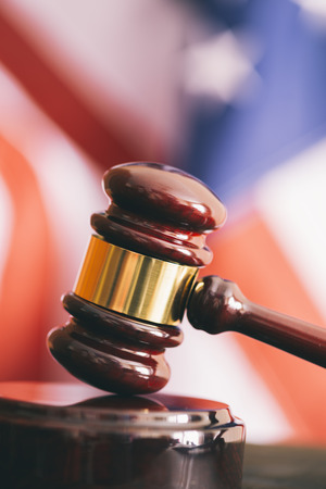 proceedings: Gavel and american flag, symbol for jurisdiction , selective focus