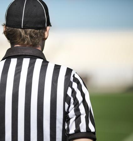 arbitros: parte trasera de un árbitro de fútbol en el primer plano, atención selectiva