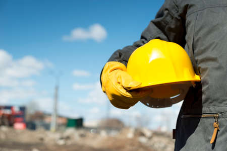 safety helmet: builder with yellow hardhat and gloves, selective focus