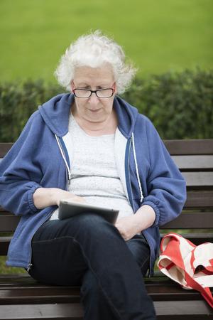 persona de la tercera edad: Superior de la mujer con tablet pc en la calle. Foto de archivo