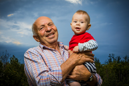 pensionary: Grandfather holding grandson outdoors, against a sunset sky, smiling.