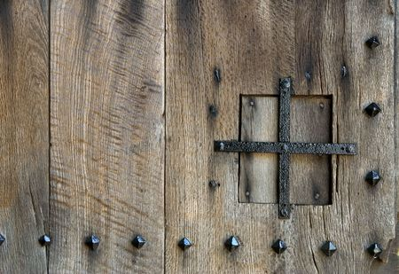 An ancient wooden door detail; peephole and nails