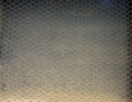 A dirty dusty window covered with a wire Stock Photo - 721530