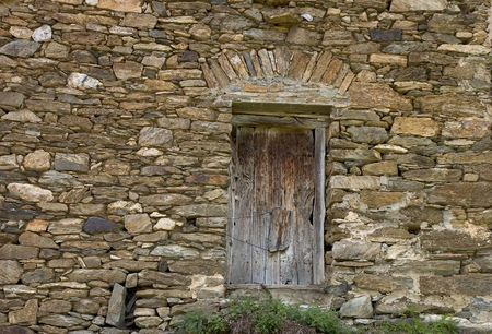 An aged wooden door in an ancient house photo
