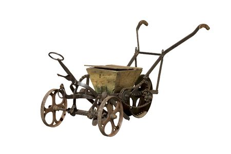 An ancient rusty seeder, isolated on white Stock Photo
