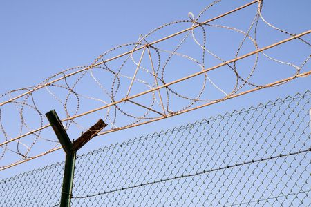 Chain link fence and barbed wire against blue sky Stock Photo - 836481