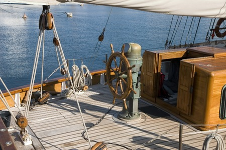wheelhouse: Steering wheel on the deck of a wood sailboat Stock Photo