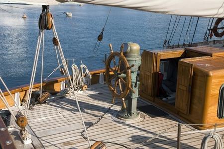 wheelhouse: Steering wheel on the deck of a wood sailboat Stock Photo