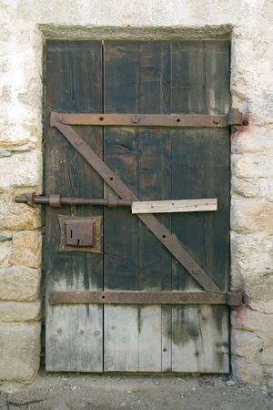 Ancient wooden door closed with a slide bolt latch