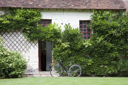 french doors: traditional Loire valley house with a bike near the entrance, France