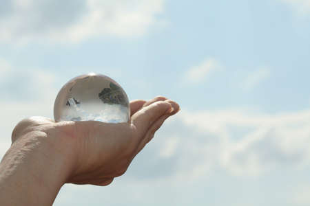 conceptional: glass globe in hand Stock Photo