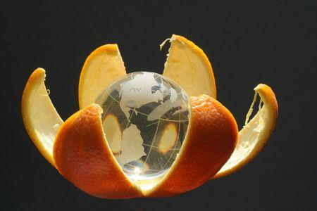 orange peel: glass globe in orange peel Stock Photo