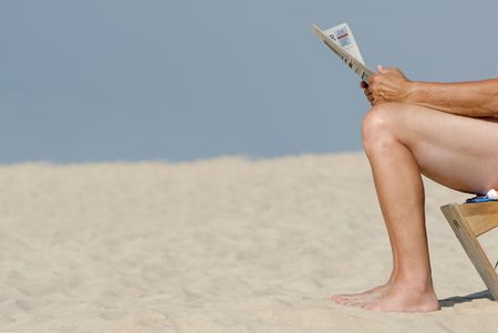 recuperation: Business man with newspaper at the beach