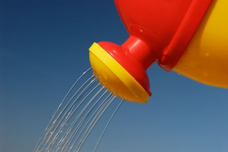 slantwise: Colourful watering can in front of blue sky