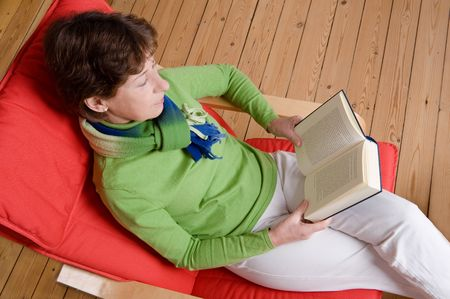 Middle aged woman is reading a book. Studio picture photo