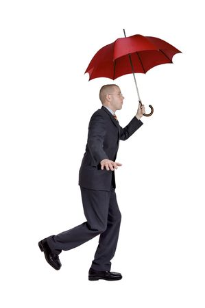 Walking businessman with a red umbrella. Full isolated studio picture photo