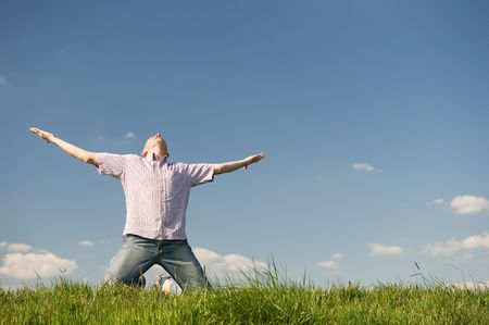 look up: Happy young man is raising his arms into the sky