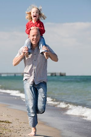 Young father with his daughter running at the beach