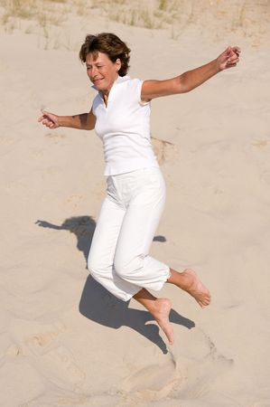 Active senior woman with white clothes is jumping through the sand. Stock Photo - 3640889