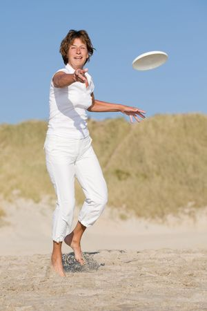 activ: Active senior woman is tossing a frisbee at the beach