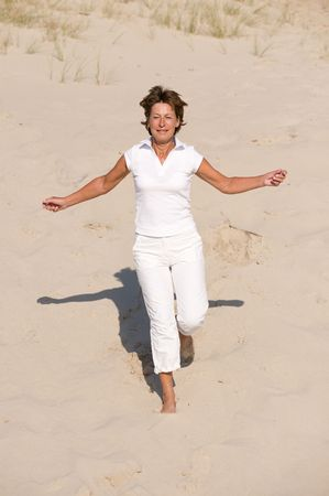 activ: Active senior woman with white clothes is jumping through the sand.  Stock Photo