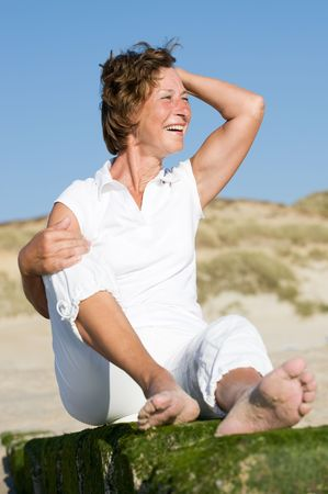 activ: Senior woman sitting on a stone at the beach. Sunset time Stock Photo