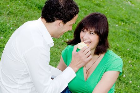 Young couple eating an apple in a park photo