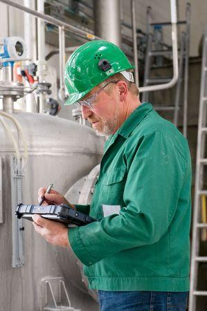 industrial mechanics: De mediana edad trabajador industrial con bloc de notas