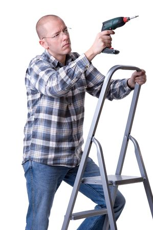 Full isolated studio picture from a young craftsman on a ladder with a cordless screwdriver photo