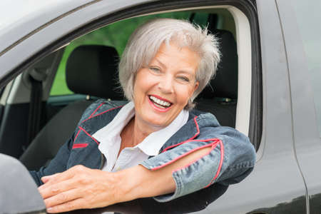 Happy and smiling senior woman in black car photo
