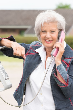 Smiling senior woman at the phone in front of a building photo