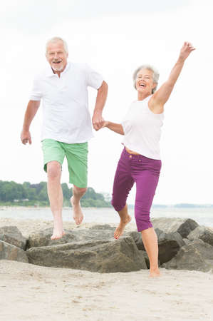 elderly couples: Active and sporty senior couple at the beach