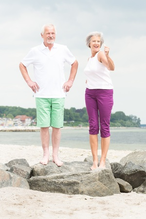 standing stones: Happy and smiling senior couple at the beach Stock Photo