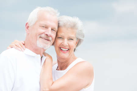 an elderly couple: Happy and smiling couple in front of cloudy sky Stock Photo