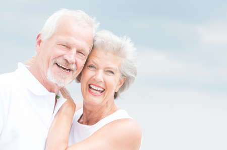 Happy and smiling couple in front of cloudy sky Stock Photo