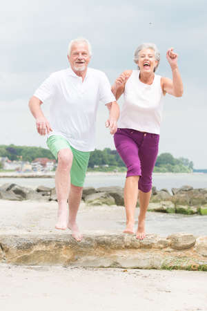 senior health: Active and sporty senior couple at the beach