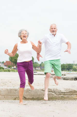 elderly exercise: Active and sporty senior couple at the beach