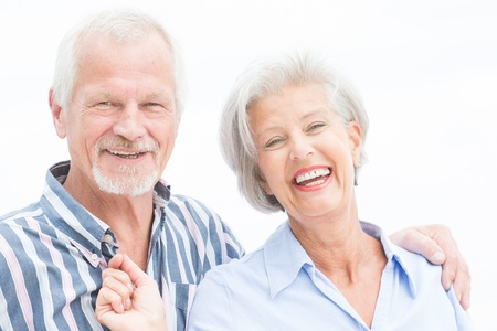 happy couple white background: Portrait from a happy senior couple in front of cloudy sky