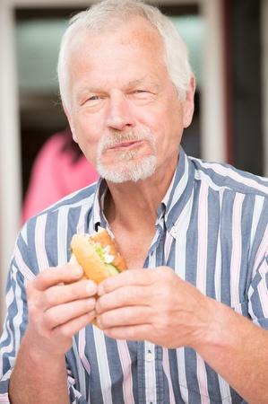 Smiling senior amn eating some fish photo