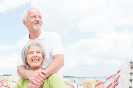 happy couple white background: Smiling senior couple at the beach