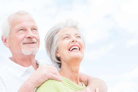 60s adult: Portrait from a happy senior couple in front of cloudy sky